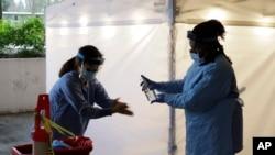 지난 13일 미국 시애틀의 워싱턴대병원에서 간호사들이 드라이브 스루 코로나 감염 검사를 진행하고 있다.