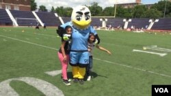 Two refugees girls take a photo with DC United's mascot, Talon. (June Soh)