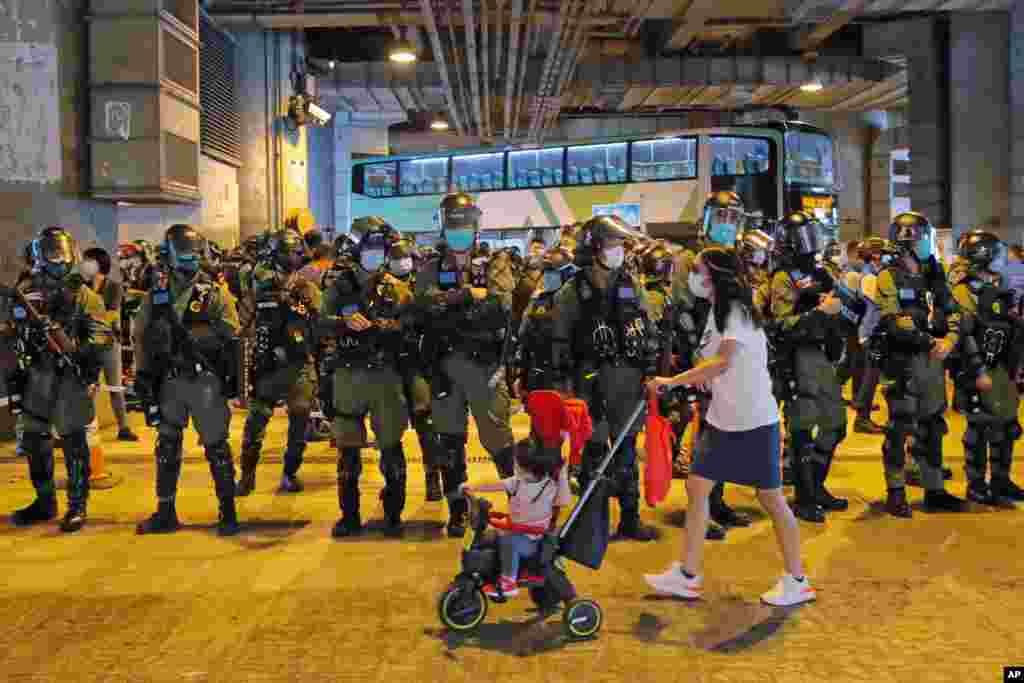 گروهی از پلیس های ضد شورش در مقابل محل تجمع گروهی از دموکراسیخواهان در هنگ کنگ تجمع کرده اند. معترضان به دخالت چین در امور هنگ کنگ معترض هستند.