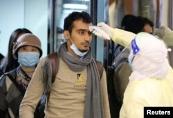 Passengers coming from China wearing masks to prevent transmission of a new coronavirus are checked by Saudi Health Ministry employees upon their arrival at King Khalid International Airport, in Riyadh, Saudi Arabia, Jan. 29, 2020.