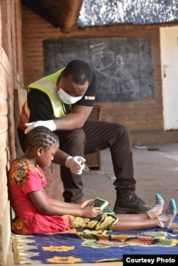 Charity Kanyoza, an education specialist at British charity Voluntary Services Overseas, assists a student with a computer tablet at her home in Lilongwe, Malawi. (Photo courtesy of VSO/Craig Mawanga)