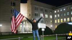 Marianne Hoenow from the U.S. state of Connecticut celebrates the victory of President-elect Joe Biden and Vice President-elect Kamala Harris in front of the U.S. Embassy next to the Brandenburg Gate in Berlin, Germany, Nov. 7, 2020.