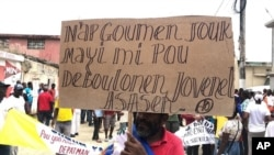 """Protester in Port-de-Paix, Haiti holds sign that reads: """"We'll fight until the corn gets ripe to untangle ourselves from killer Jovenel"""", during a protest to demand the president resign, Oct. 4, 2019. (Photo: Lucson Palmeus / VOA Creole)"""