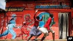 Children run down a street past an informational mural warning people about the dangers of the COVID-19 coronavirus, in the Kibera slum of Nairobi, Kenya on Wednesday, June 3, 2020. (AP Photo/Brian Inganga)