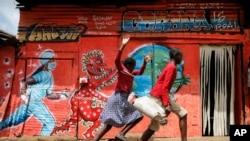 Yon miral nan Peyi Kenya ki atire atansyon timoun yo sou danje kowonaviris poze nan kominote yo. (Foto: AP/Brian Inganga. 3 jen 2020)