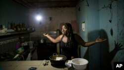 FILE- Dugleidi Salcedo complains to a neighbor about the high price of food as she prepares arepas for her three sons in her kitchen in the Petare slum, in Caracas, Venezuela, Feb. 14, 2019.