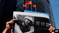 A protester holds a photo of Chow Tsz-Lok during a memorial flash mob to remember him near Chinese and Hong Kong flags in Hong Kong on Friday, Nov. 8, 2019. Chow, a Hong Kong university student who fell off a parking garage after police fired tear…