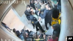 In this frame grab taken from video shared with AP by 'The Justice of Ali,' a guard beats a prisoner, at Evin prison in Tehran, Iran. (The Justice of Ali via AP)