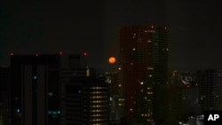 Tokyo's skyline is seen through the window of a hotel as the moon sets on July 23, 2021, in Tokyo. The opening ceremonies for the 2020 Summer Olympics are set for Friday.