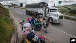 Los migrantes venezolanos descansan mientras caminan hacia Bogotá, en Tunja, Colombia, el martes 6 de octubre de 2020.