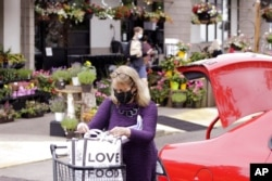 FILE - A woman wearing a mask loads groceries into her car in Portland, Ore., May 21, 2021. As the federal government and many states eased rules on mask-wearing and business occupancy this year, some blue states largely stuck with them.