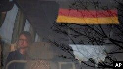 Turis Jerman yang terlantar duduk di sebuah bis yang membawanya ke bandara internasional di Kathmandu, Nepal, 27 Maret 2020.
