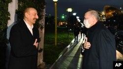 Presiden Azerbaijan Ilham Aliyev (kiri) menyambut hangat kedatangan Presiden Turki Recep Tayyip Erdogan dalam jamuan resmi makan malam di Baku, Azerbaijan, Rabu (9/12).