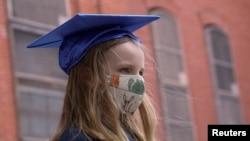 La niña Lydia Hassbroek se prueba su virrete para una fotografía para su graduación digital, en medio de la pandemia del coronavirus en Brooklyn, Nueva York. 11 junio de 2020.