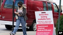 A woman wears a face mask as she walks past an information sign of COVID-19 testing in Chicago, Ill., Aug. 13, 2021.