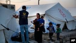 Sirijka sa decom, porodica raseljena zbog turske vojne operacije u severoistočnoj Siriji sa kurdskim humanitarnim radnicima u kampu severno od Mosula u Iraku, 16. oktobra 2019.
