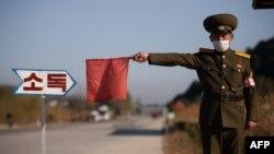 Arhiva - Pripadnik sjevernokorejske javne bezbjednosti zaustavlja taksi radi dezinfekcije, u sklopu napora protiv širenja Covida-19, na putu na ulazu u Vosan, pokrajina Kangvon, Sjeverna Koreja, 29. oktobra 2020