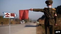 Arhiva - Pripadnik severnokorejske javne bezbednosti zaustavlja taksi radi dezinfekcije, u sklopu napora protiv širenja Kovida 19, na putu na ulazu u Vosan, pokrajina Kangvon, Severna Koreja, 29. oktobra 2020