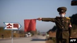 Seorang petugas ketertiban umum mengacungkan bendera merah untuk menghentikan sebuah taksi untuk dibersihkan dengan disinfektan sebagai pencegahan wabah COVID-19 jalan masuk Wonsan, Provinsi Kangwon, Korea Utara, 29 Oktober 2020.