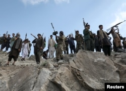 FILE - Armed men attend a gathering to announce their support for Afghan security forces and their willingness to fight against the Taliban, on the outskirts of Kabul, Afghanistan, June 23, 2021.