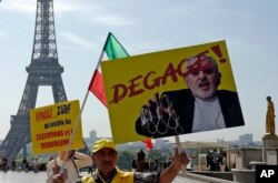 Demonstrators of the National Council of Resistance of Iran demonstrate on the Trocadero square Friday, Aug. 23, 2019 in Paris as Iranian Foreign Minister Javad Zarif is in France. Poster reads: get out.