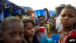 FILE - A girl balances a bowl of food on her head at an Internally Displaced People's (IDP) camp in Faladie, where hundreds have found refuge after fleeing inter-communal violence in central Mali, May 14, 2019.