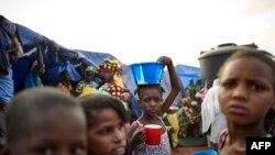 Une fille met en équilibre un bol de nourriture sur sa tête dans un camp de personnes déplacées à l'intérieur du camp de Faladie, où des centaines de personnes ont trouvé refuge après avoir fui la violence intercommunautaire dans le centre du Mali, le 14 mai 2019.