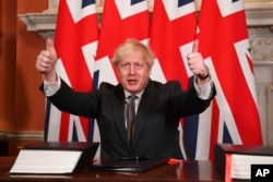 Britain's Prime Minister Boris Johnson gives a thumbs-up gesture after signing the EU-UK Trade and Cooperation Agreement at 10 Downing Street, London, Dec. 30, 2020.