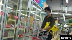 一名男子戴口罩在超市選購冷凍食品。(2020年8月13日)