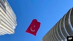 Un drapeau turc suspendu entre deux gratte-ciel flotte au vent, à Istanbul, jeudi 23 avril 2020.