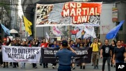 A policeman takes a picture of activists as they march to mark the second year of martial law in Mindanao, during a rally near the Malacanang palace in Manila, Philippines on Friday, May 24, 2019. The group is calling for an end to martial law in…