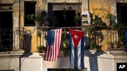 FILE - U.S. and Cuban flags hang from a balcony in Old Havana, Cuba, Dec. 19, 2014.