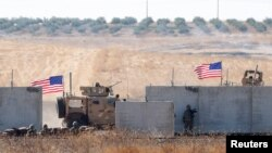 FILE - U.S. troops are seen behind the Turkish border walls in northern Syria, Sept. 8, 2019.