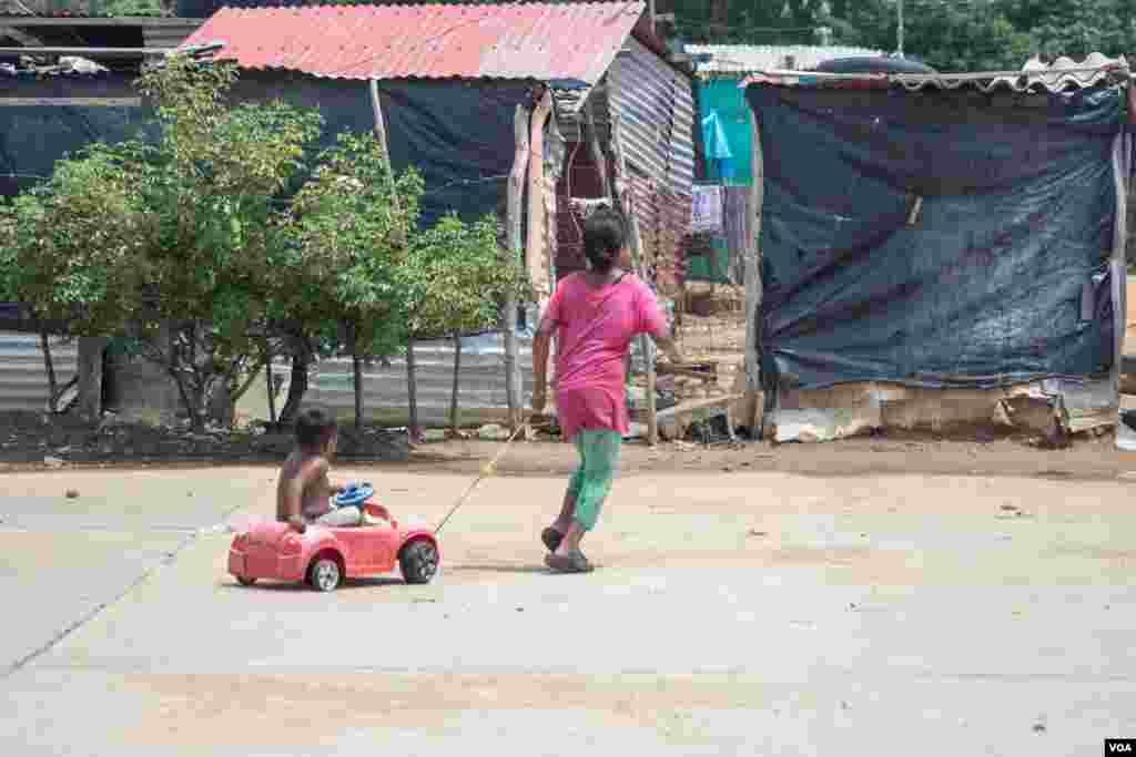 Una niña jala en su carrito a su hermano en La Pista, una zona cerca de la frontera colombo-venezolana en donde familias venezolanas viven bajo extremas condiciones de pobreza.