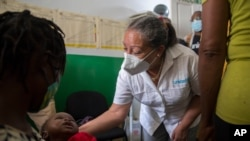 Jean Gough, UNICEF regional director for Latin America and the Caribbean, greets an infant in a malnutrition clinic in Les Cayes, Haiti, May 26, 2021.