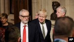 ທ່ານ Boris Johnson, ນາຍົກຂອງອັງກິດ (ກາງຂວາ) ແລະ ທ່ານ Jeremy Corbyn, ຫົວໜ້າພັກແຮງງານ ຊຶ່ງເປັນພັກຝ່າຍຄ້ານ ກຳລັງພາກັນຍ່າງຜ່ານຫ້ອງໂຖງຂອງສະພາຕ່ຳ ໃນໄລຍະທີ່ມີການເປີດກອງປະຊຸມຫລວງຂອງສະພາໃນນະຄອນຫລວງລອນດອນ, ວັນທີ 19 ທັນວາ, 2019