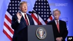 2018年7月12日特朗普(左)和博尔顿在比利时布鲁塞尔北约总部举行的国家元首和政府首脑峰会之后的新闻发布会上