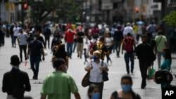 Ciudadanos con tapabocas en medio de la pandemia de coronavirus caminan por el bulevar de Sabana Grande en Caracas, Venezuela. Junio 17, 2020.