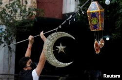 Seorang pria meletakkan dekorasi Ramadhan di jalan menjelang bulan suci Muslim, selama lockdown akibat COVID-19 di Beirut, Lebanon, 19 April 2020. (Foto: Reuters)