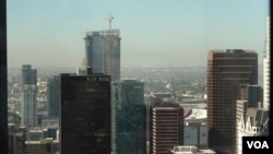 A photo of downtown Los Angeles skyline with the towering Oceanwide Plaza seen in the background with a crane. The Beijing-based developer Oceanwide Holdings suspended the L.A. project in January.