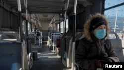 A woman wearing a face mask sits inside a public bus, as the country is hit by an outbreak of the novel coronavirus, in Beijing, China February 15, 2020. REUTERS/Stringer NO RESALES. NO ARCHIVES.