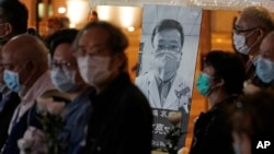 People wearing masks, attend a vigil for Chinese doctor Li Wenliang, in Hong Kong, Friday, Feb. 7, 2020. The death of a young doctor who was reprimanded for warning about China's new virus triggered an outpouring Friday of praise for him and fury…