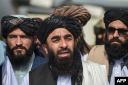 Taliban spokesman Zabihullah Mujahid, center, addresses a media conference at the airport in Kabul on Aug. 31, 2021.