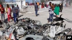 FILE - Somalis walk past debris after a suicide car bomb attack on a government building in the capital Mogadishu, Somalia, Saturday, March 23, 2019. Al-Shabab gunmen stormed the government building after the bomb attack.
