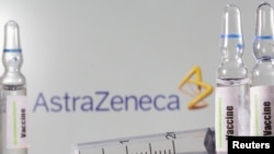 A test tube labeled with the Vaccine is seen in front of AstraZeneca logo in this illustration, Sept. 9, 2020.