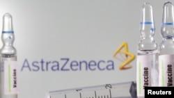 ຫຼອດຢາທົດລອງ ທີ່ມີກາຂອງຢາວັກຊີນ ທີ່ເຫັນໄດ້ຕັ້ງຢູ່ຕໍ່ໜ້າ ສັນຍາລັກ ຂອງບໍລິສັດ AstraZeneca ໃນພາບທີ່ສະແດງອັນນີ້, ວັນທີ 9 ກັນຍາ 2020.