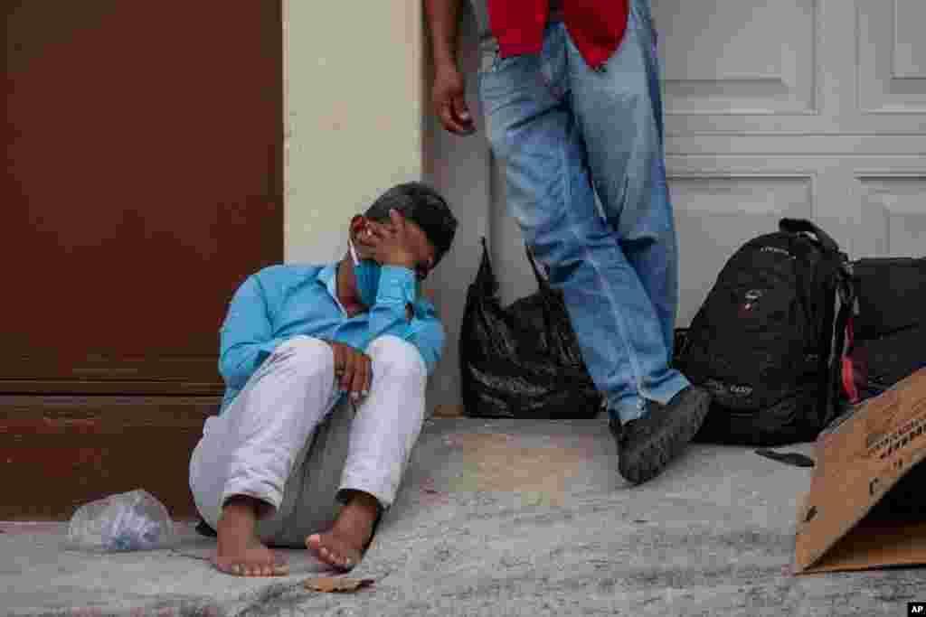 '야간 통행 금지령'이 내려진 과테말라 수도 과테말라시티에서 신종 코로나바이러스 감염증(COVID-19)을 막기 위해 마스크를 착용한 노숙자가 통금 시간 전 임시 쉼터에 들어가기 위해 대기하고 있다.