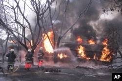 Fire fighters try to extinguish a Petrol Tanker blaze, Aug. 10 2019, in Morogoro, Tanzania.