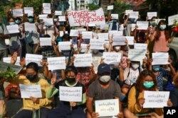 Para pengunjuk rasa memegang slogan yang mengutuk pemerintah militer dalam festival Thingyan, Selasa, 13 April 2021 di Yangon, Myanmar.