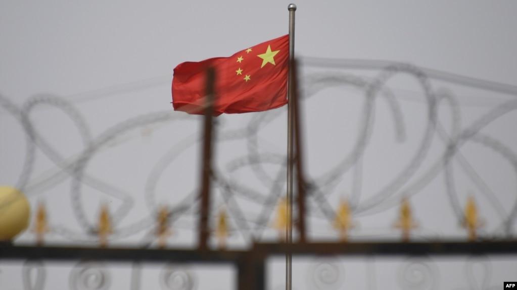 资料照片:在新疆喀什市以南的一个居住区,一面中国国旗在铁丝网后面飘扬。(2019年6月4日)(photo:VOA)